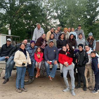 A large family is gathered for a hay ride at Wolf Lake Ranch!