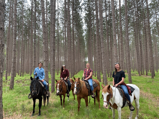 Four girls riding horses in the Manistee National Forest while visiting Wolf Lake Ranch.